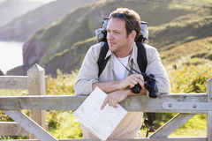 Man relaxing on cliffside path holding map Royalty Free Stock Photo