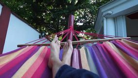 Man relaxing on a colorful hammock in a summer day. Young guy lying down taking a nap. Crossing legs in long blue hippie pants. Tr