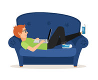 Man relaxing on couch and browsing social media or Royalty Free Stock Images