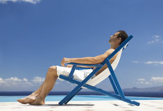 A man relaxing in a deck chair Royalty Free Stock Images