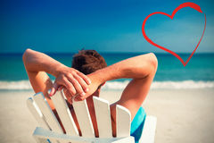 Man relaxing on deck chair at the beach Stock Photography