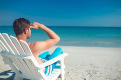 Man relaxing on deck chair at the beach Royalty Free Stock Photo