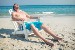 Man relaxing on deck chair at the beach Stock Image
