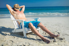 Man relaxing on deck chair at the beach Stock Images