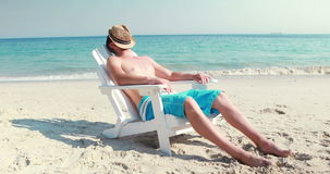 Man relaxing on deck chair at the beach. On a sunny day stock video footage