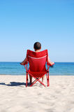 Man relaxing on deckchair at the beach. Adult sat on sunbed by the sea Stock Photography