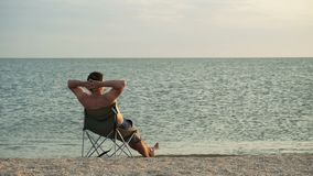 Man relaxing on deckchair on beach stock footage