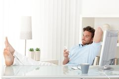 Man relaxing at desk, texting on phone. Man sitting relaxing at desk, bare feet on table, texting on mobile phone stock images