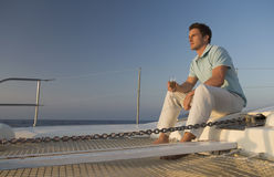 A man relaxing with a drink on a boat Stock Photo