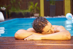 Man relaxing on edge of pool Royalty Free Stock Photography