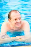 man relaxing by the edge of the swimming pool royalty free stock images