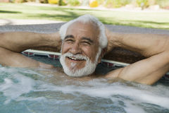 Man Relaxing At The Edge Of Swimming Pool Royalty Free Stock Photos