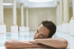 Man Relaxing On Edge Of Swimming Pool Stock Images