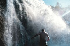 Man relaxing with freedom banner. Person with open arms in waterfall in Ural nature. Stock Photo
