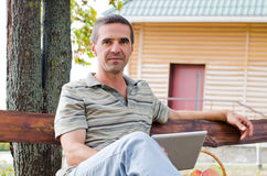 Man relaxing on a garden bench Stock Photography