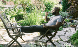 Man Relaxing in  Garden with  Wine Royalty Free Stock Image
