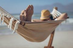 Man relaxing on hammock at beach stock photo