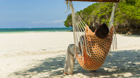 Man relaxing in a hammock on the beach on holidays. Stock Photos