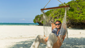 Man relaxing in a hammock on the beach on holidays. Stock Images
