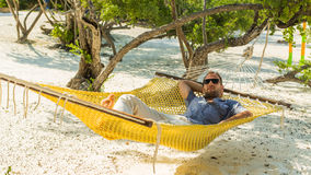 Man relaxing in a hammock on the beach on holidays. Stock Photography