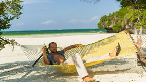 Man relaxing in a hammock on the beach on holidays. He is drinki Royalty Free Stock Image