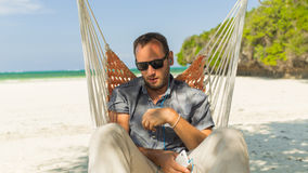 Man relaxing in a hammock on the beach on holidays. He is listen Royalty Free Stock Photography