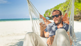 Man relaxing in a hammock on the beach on holidays. He is listening music Royalty Free Stock Photography