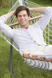 Man relaxing in hammock smiling Royalty Free Stock Photos