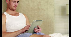 Man relaxing in his bed using tablet pc. In bedroom stock video footage