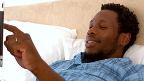 Man relaxing in his bed using tablet pc. In slow motion stock video footage