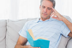 Man relaxing on his couch with a book Royalty Free Stock Photos