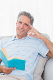 Man relaxing on his couch with a book smiling at camera Royalty Free Stock Images