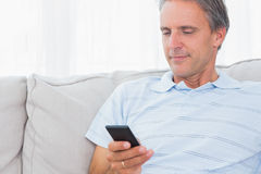Man relaxing on his couch sending a text Royalty Free Stock Images