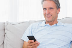 Man relaxing on his couch sending a text smiling at camera Royalty Free Stock Image