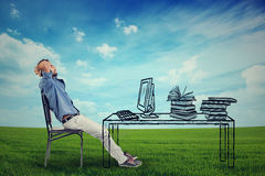 Man relaxing at his desk outdoors Stock Images