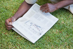 Man relaxing in his garden reading newspaper Royalty Free Stock Photography