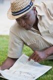 Man relaxing in his garden reading newspaper Stock Image