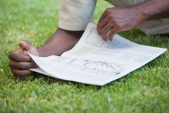 Man relaxing in his garden reading newspaper Stock Images