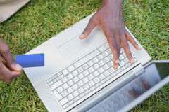 Man relaxing in his garden using laptop to shop Royalty Free Stock Image