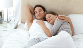 Man relaxing with his girlfriend. Man dreaming on his bed while relaxing with his girlfriend at home Royalty Free Stock Photo