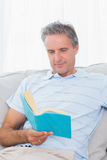 Man relaxing on his sofa with a book Royalty Free Stock Photo