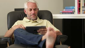 Man relaxing with his tablet Royalty Free Stock Photos