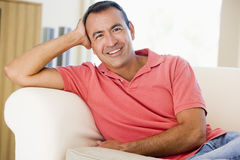 Man relaxing at home. Multi-racial smiling man relaxing on a couch at home Royalty Free Stock Image