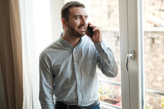 Man relaxing at home and calling with phone. Man relaxing at home and have a conversation with someone stock image