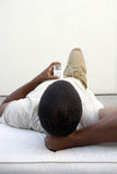 Man relaxing at home, lying on back, listening to MP3 player, rear view Stock Photos