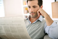 Man relaxing at home with newspaper in hands Stock Photos