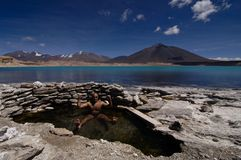 Man relaxing in hot springs by glacier lake Royalty Free Stock Image