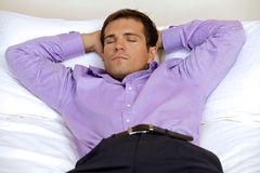 Man relaxing in hotel room with hands behind head, eyes closed Royalty Free Stock Photo
