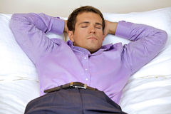 Man relaxing in hotel room with hands behind head, eyes closed royalty free stock images