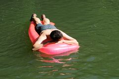 Man relaxing on inflatable Stock Images